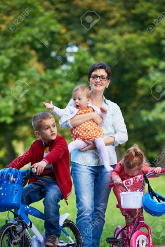 42403614-family-portrait-outdoor-in-park-modern-mom-with-kids-child-learning-to-ride-bike
